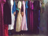Children peeking out from rack of fancy dresses