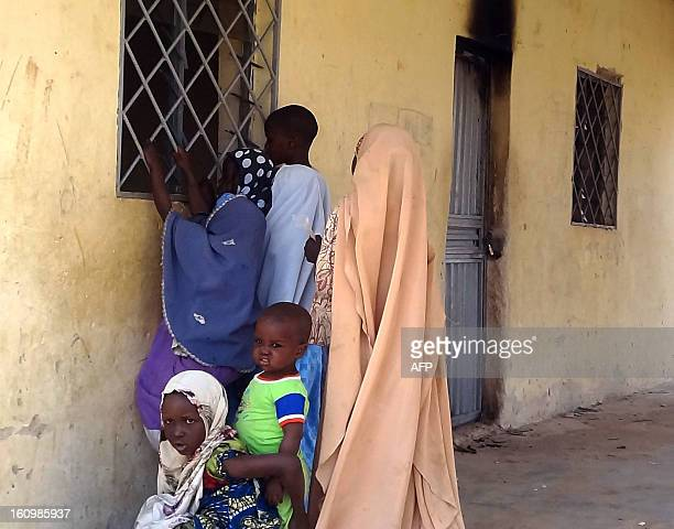 Children peep througth the iron bars on the window of the locked off Haye dispensary on February 8 2013 in the northern Nigerian city of Kano where...