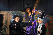 Children (4-9) performing on stage, portrait of girl in witches costume