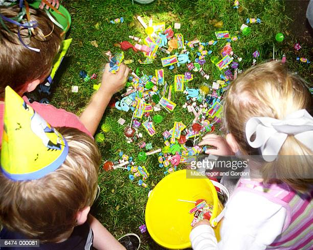 Children Pick Candies off Lawn