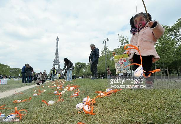 Children pick eggs during an Easter egg hunt organised by the Secours Populaire in front of the Eiffel Tower at the ChampdeMars in Paris on April 20...