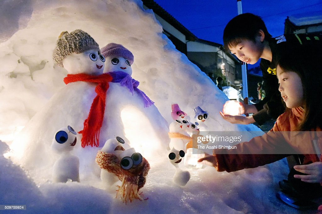 Children place candles in front of the snowmen during the Snowman Festival 2016 in Hakusan, Ishikawa, Japan.