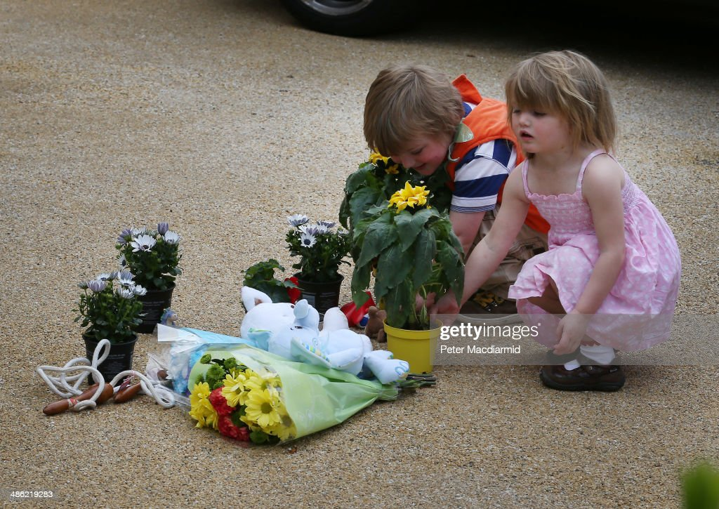 Children place flowers on the drive of a house in New Malden where the bodies of three children were found on April 23, 2014 in south London, England. Police say that a 43 year old woman has been arrested after the bodies of three children were found at a property last night.