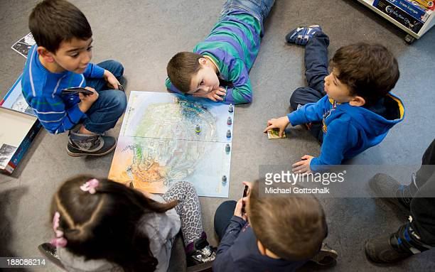 Children play a board game during the presentation of Project 'Lesestart' in a Libary for Children on November 15 2013 in Berlin Germany The Project...
