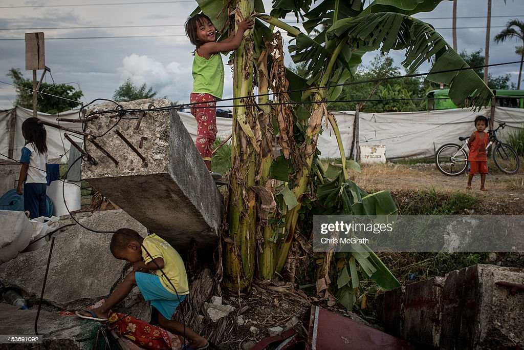 Children play a game of tag amongst debris inside the San Jose evacuation complex on August 16, 2014 in Tacloban, Leyte, Philippines. Many families are still housed in temporary tent housing in the San Jose district. The families have been told that they will be rehoused before the visit of Pope Francis. Residents of Tacloban city and the surrounding areas continue to focus on rebuilding their lives nine months after Typhoon Haiyan struck the coast on November 8, 2013, leaving more than 6000 dead and many more homeless. With many businesses and government operations back up and running and with the recent start of the years typhoon season, permanent housing continues to be the main focus with many families still living in temporary accommodation. As well as continuing recovery efforts Leyte is preparing for the arrival of Pope Francis, who will visit the region from January 15- 19.