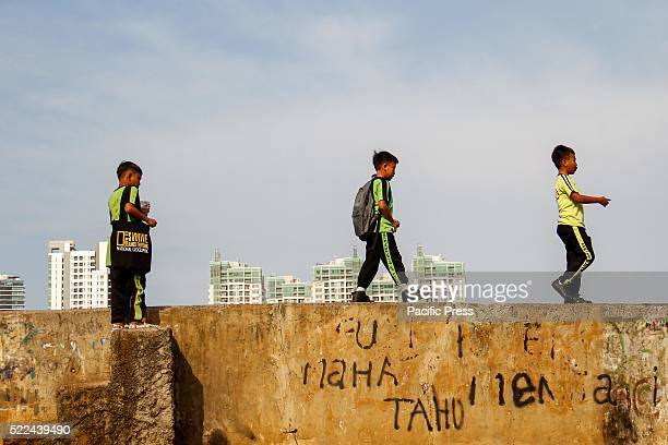 Children play along the riverbank as high rise buildings are seen in the background