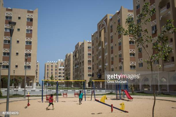 Children play amongst the newly built apartment blocks of the Qatarifunded Sheikh Hamad residential project in Khan Younis on July 24 2017 in Khan...