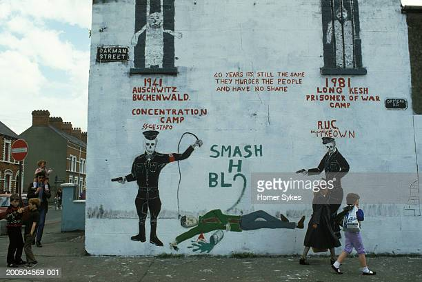 Children play and walk past a Catholic political wall painting during the Troubles It likens the H block at Long Kesh prison as being similar to a...