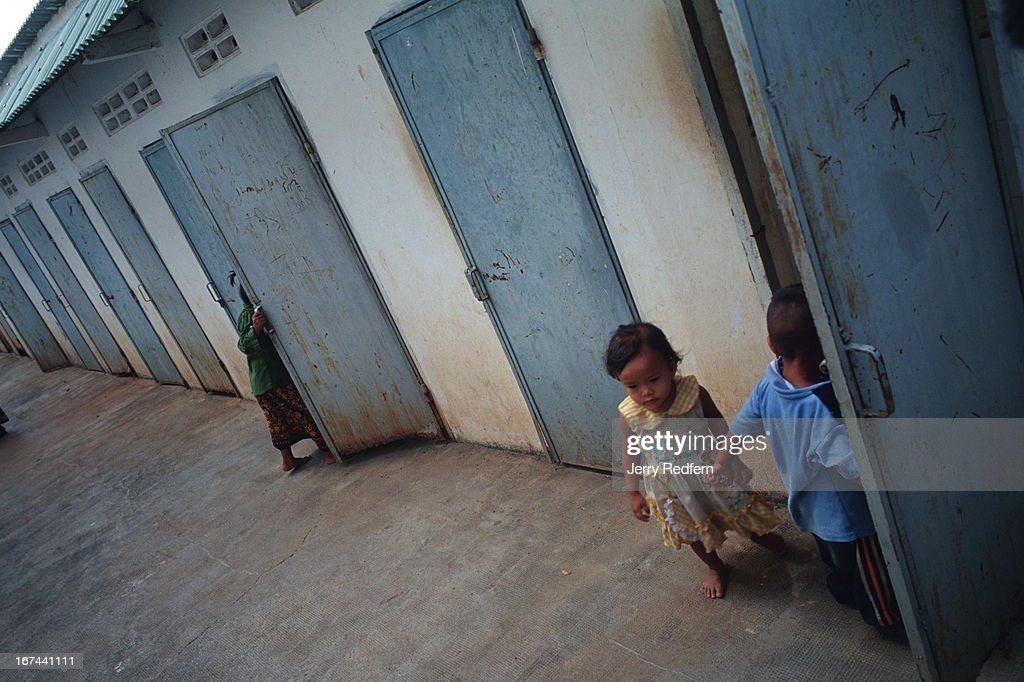 Children play around broken and abandoned shower stalls near...