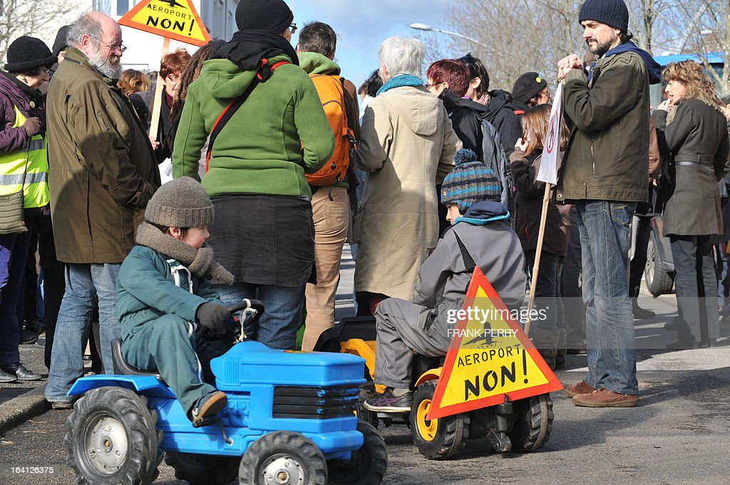 Children play around placards reading 'Airport, No !' as opponents of the Notre-Dame des Landes airport demonstrate on March 20, 2013 outside the Saint-Nazaire courthouse. AFP PHOTO / FRANK PERRY