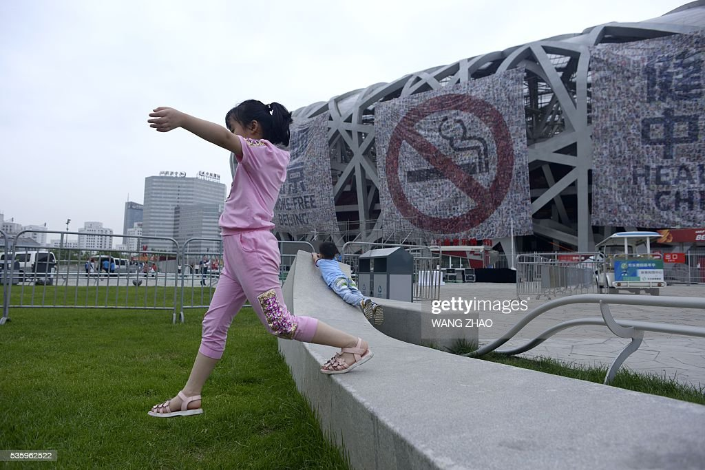 Children play as a giant poster for World No Tobacco Day is seen at the National Olympic Stadium or 'Birds Nest' in Beijing on May 31, 2016. May 31 is observed as World No Tobacco Day, with the World Health Organisation (WHO) using 'Get Ready For Plain Packaging' as the slogan of this year's day. / AFP / WANG