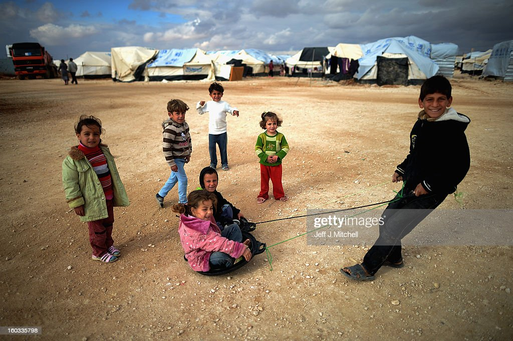 Children play as Syrian refugees go about their daily business in the Za'atari refugee camp on January 29 2013 in Mafraq Jordan Record numbers of...