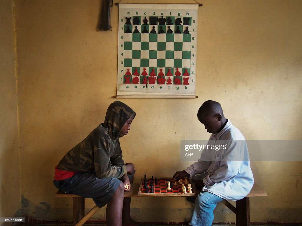 Children play at a chess centre in Kampala on January 30, 2013. Club member, Phiona Mutesi went from living rough on the streets of a Kampala slum to competing in chess' most prestigious international tournaments. Mutesi is the first female Ugandan to reach the level of candidate master and the country's reigning under 20 champion. Disney film studios have bought the option to turn her story into a movie. Since starting in 2003 the chess club has moved from playing chess with bottle tops to having a basic club house and over 60 members. AFP PHOTO/Michele Sibiloni