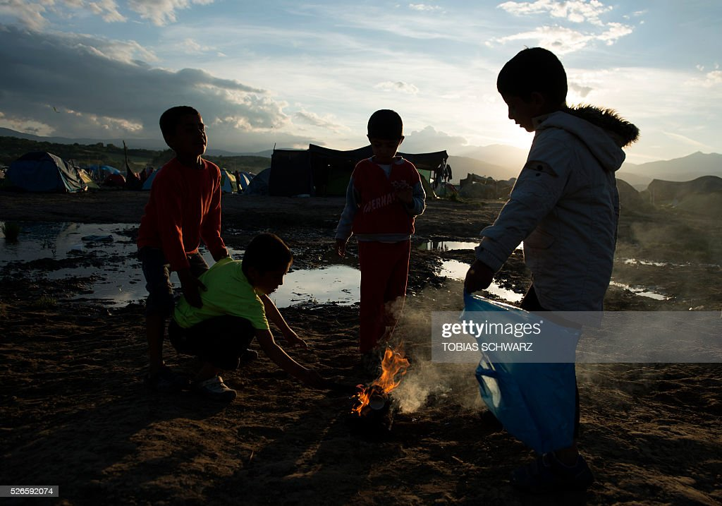 Children play at a fire at a makeshift camp for migrants and refugees near the village of Idomeni not far from the Greek-Macedonian border on April 30, 2016. Some 54,000 people, many of them fleeing the war in Syria, have been stranded on Greek territory since the closure of the migrant route through the Balkans in February. / AFP / TOBIAS
