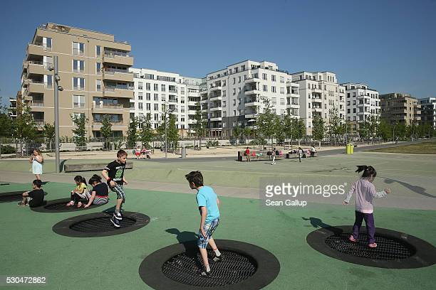 Children play at a playground near newlycompleted apartment buildings at Gleisdreieck park in the city center on May 11 2016 in Berlin Berlin Berlin...