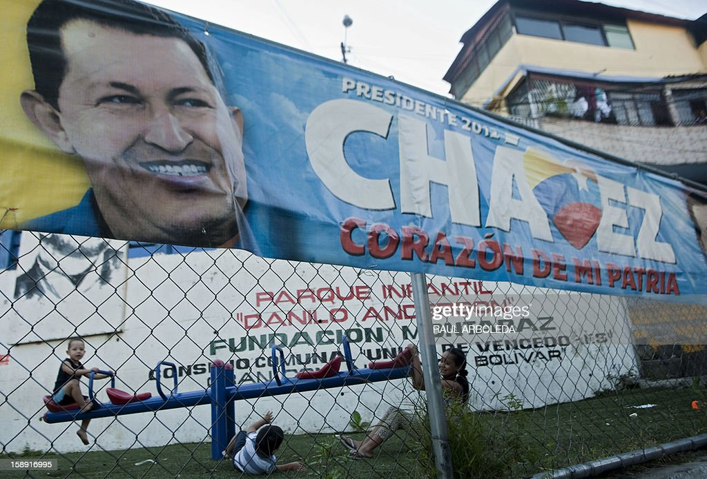 Children play at park next to a banner with the image of Venezuelan President Hugo Chavez in Caracas, on January 3, 2013. Top Venezuelan officials returned to Venezuela after gathering in Cuba amid mounting concern about the health of cancer-stricken President Hugo Chavez, just days before he is to be sworn in for another term. AFP PHOTO/Raul ARBOLEDA