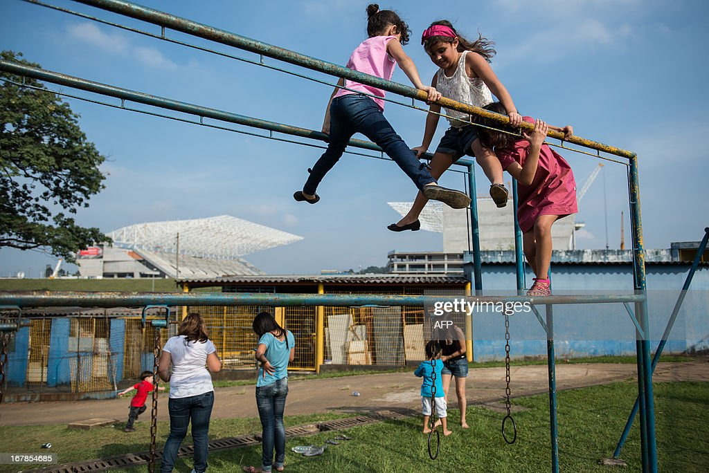 Children play at play near the Itaquerao Stadium (Corinthians Arena) in Sao Paulo, Brazil on May 1, 2013. The stadium has been completed 70 % of the process and will host the opening match of FIFA World Cup 2014. AFP PHOTO/Yasuyoshi CHIBA