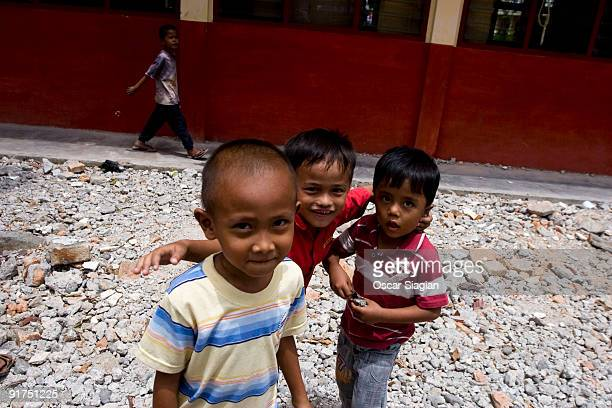 Children play at s collapsed school on October 11 2009 in Padang Indonesia Extensive parts of West Sumatra were destroyed during the 76 magnitude...