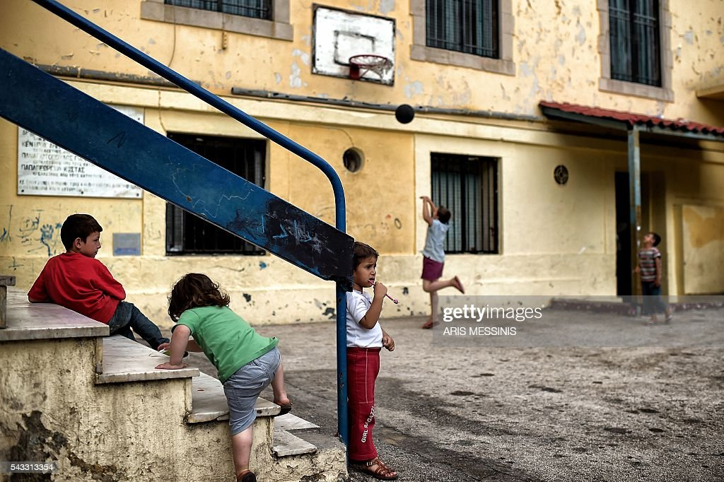 Children play at the yard of an abandoned school used by volunteers for hosting families of refugeees from Syria and Afghanistan in Athens on June 27, 2016. / AFP / ARIS