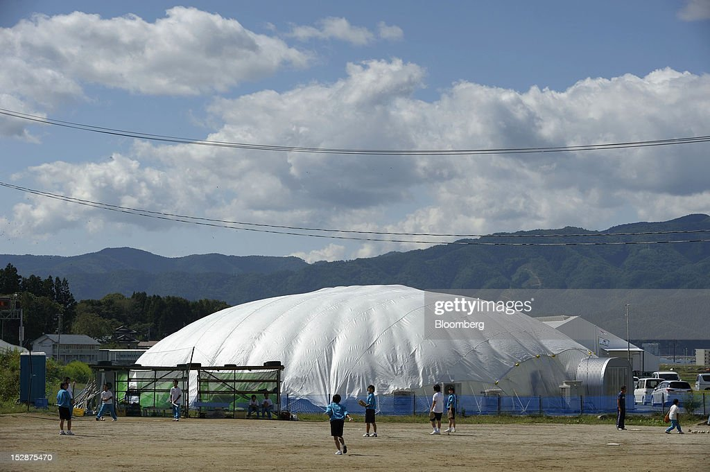 Children play baseball in front of a dome-shaped vegetable plant at Granpa Farm Rikuzentakata, in Rikuzentakata City, Iwate Prefecture, Japan, on Wednesday, Sept. 26, 2012. A total of 8 dome-shaped hydroponic vegetable plants operated by Granpa Farm Rikuzentakata, a group farming subsidiary of Granpa Co. which was opened last month as part of the region's reconstruction efforts in an area damaged by the tsunami following the earthquake on March 11, 2011, produces 3,600 heads of lettuce a day. Photographer: Akio Kon/Bloomberg via Getty Images