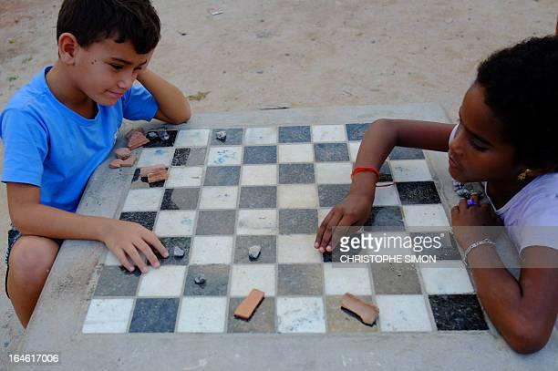 Children play checkers with stones at a public square at Cidade de Deus slum in Rio de Janeiro Brazil on March 23 2013 AFP PHOTO/CHRISTOPHE SIMON