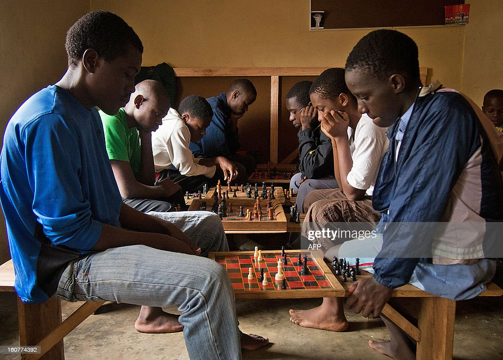 Children play chess at a chess centre in Kampala on January 30, 2013. Club member, Phiona Mutesi went from living rough on the streets of a Kampala slum to competing in chess' most prestigious international tournaments. Mutesi is the first female Ugandan to reach the level of candidate master and the country's reigning under 20 champion. Disney film studios have bought the option to turn her story into a movie. Since starting in 2003 the chess club has moved from playing chess with bottle tops to having a basic club house and over 60 members. AFP PHOTO/Michele Sibiloni