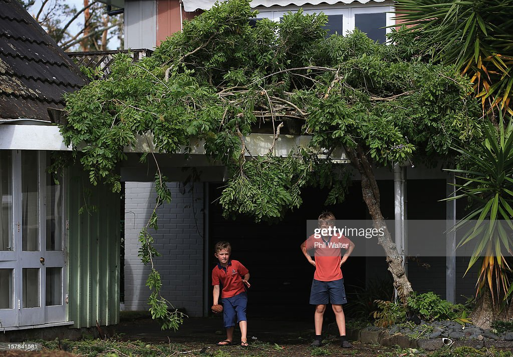 Children play cricket under storm debri in the Auckland suburb of Whenuapai following a tornado that struck yesterday on December 7, 2012 in Auckland, New Zealand. Police today named the three men killed whilst working on a construction site when the tornado hit.