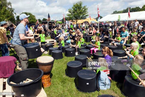 Children play drums after completing their run at the 'Children's Relay Run' where Crown Princess Mary presented medals in Faelledparken on June 10...