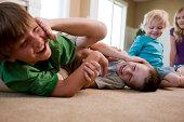 Children play fighting on floor