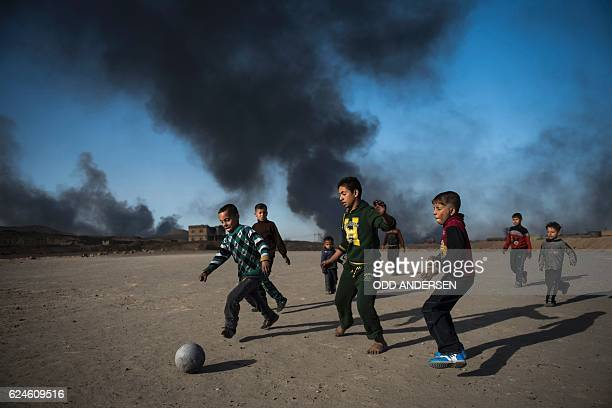 TOPSHOT Children play football as oil wells set ablaze by retreating Islamic State jihadists burn behind them in the town of Qayyarah some 70 km...