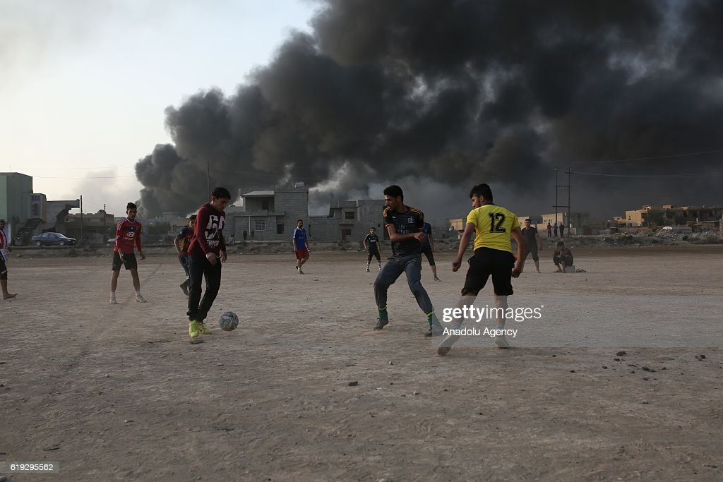 Children play football as smoke rises from oil wells, were set on fire by Daesh terrorists to limit coalition forces pilots' eyesight and to make the wells out of service following Iraqi army's retaking of Al Qayyarah town from Daesh during the operation to retake Iraq's Mosul from Daesh, in Al Qayyarah Town Mosul, Nineveh, Iraq on October 30, 2016. A much anticipated Mosul offensive to liberate the city from Daesh began midnight Sunday.