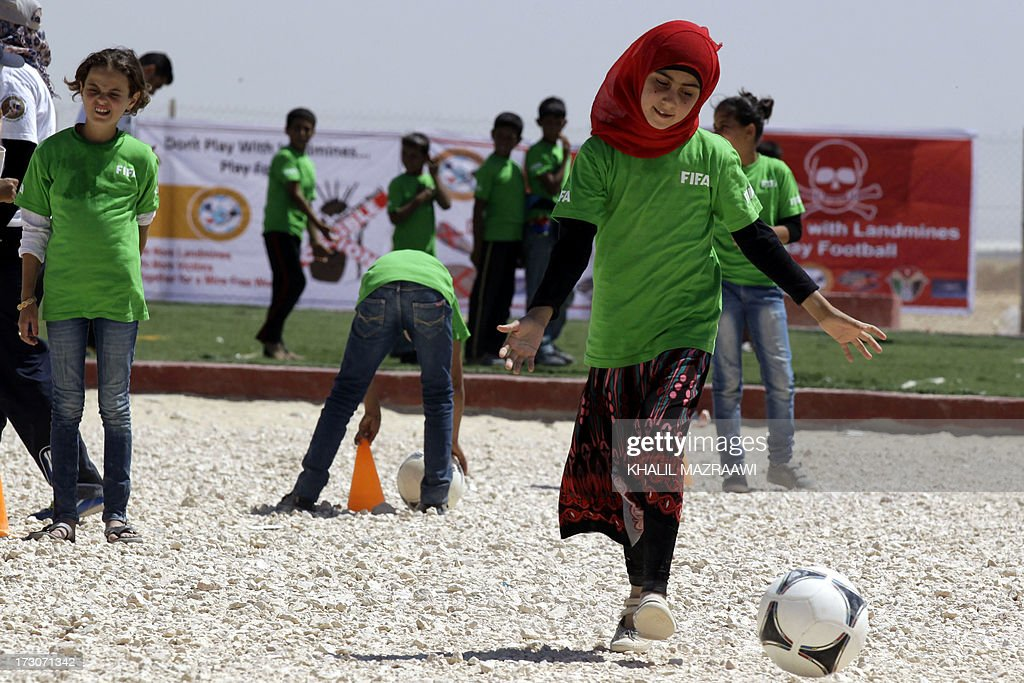 Children play football at the northern Jordanian Zaatari refugee camp on July 6, 2013 in Mafraq near the border with Syria.