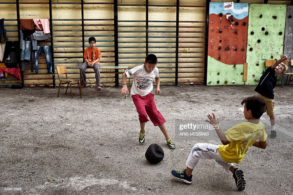 Children play football at the yard of an abandoned school used by volunteers for hosting families of refugeees from Syria and Afghanistan in Athens on June 27, 2016. / AFP / ARIS