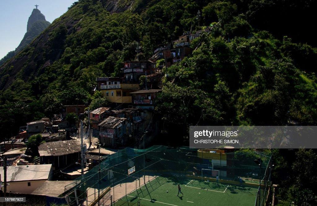 Children play football in a field in Santa Marta slum, in Rio de Janeiro, Brazil, on December 05, 2012. AFP PHOTO / CHRISTOPHE SIMON
