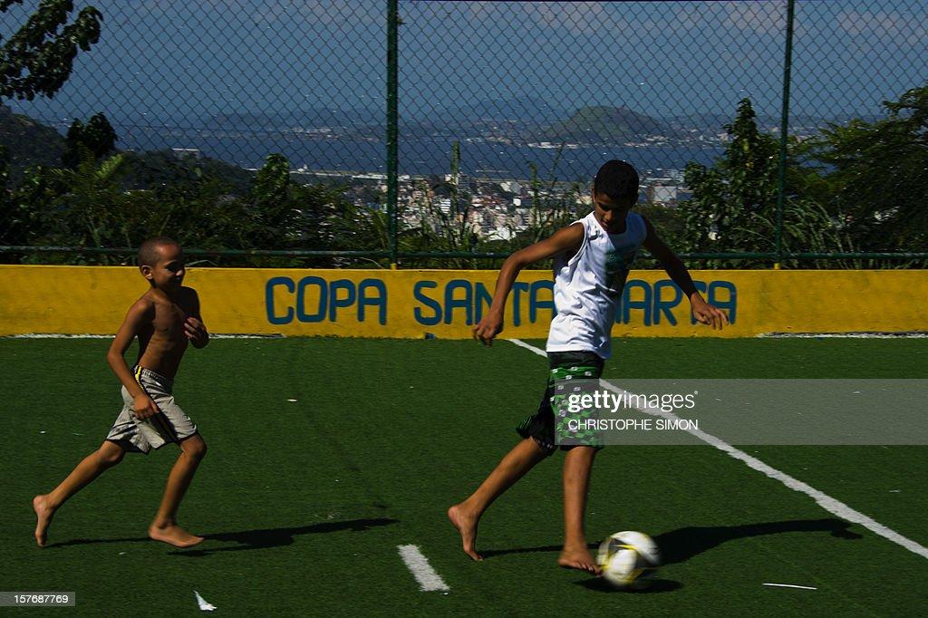 Children play football in a field in Santa Marta slum, in Rio de Janeiro, Brazil, on December 05, 2012.