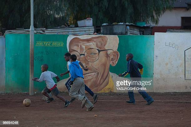 Children play football in front of a portrait of former ANC deputy President Walter Sisulu in Soweto on June 12 2009 two days ahead of the opening...
