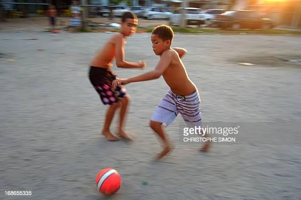 Children play football in the Cidade de Deus shantytown in Rio de Janeiro Brazil on May 11 2013 AFP PHOTO/CHRISTOPHE SIMON