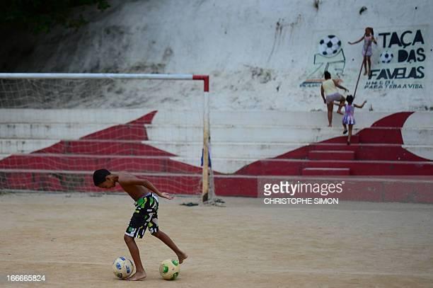 Children play football in the Cidade de Deus shantytown Rio de Janeiro Brazil on April 13 2013AFP PHOTO/CHRISTOPHE SIMON