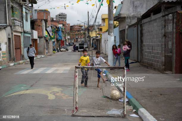 Children play football in the street in the poor neighbourhood of Itaquera adjacent to the 'Arena de Sao Paulo' stadium on June 21 2014 in Sao Paulo...
