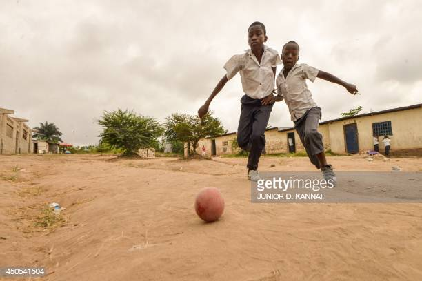 Children play football in the streets of the Kinsuka neighbourhood in the city of Kinshasa on June 10 2014 AFP PHOTO / Junior D Kannah
