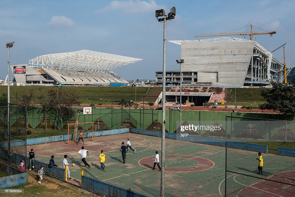 Children play football near the Itaquerao Stadium (Corinthians Arena) in Sao Paulo, Brazil on May 1, 2013. The stadium has been completed 70 % of the process and will host the opening match of FIFA World Cup 2014. AFP PHOTO/Yasuyoshi CHIBA