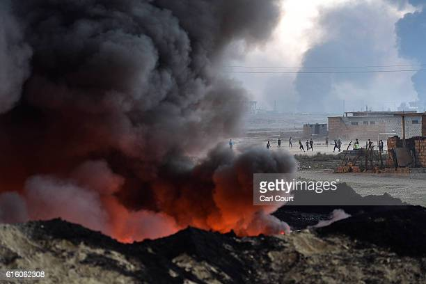 Children play football next to an oil field that was set on fire by retreating ISIS fighters ahead of the Mosul offensive on October 21 2016 in...