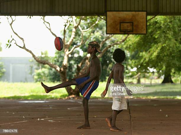 Children play football on a basketball court on December 23 2007 on the Tiwi Island Australia Kids often practice their kicking skills by trying to...