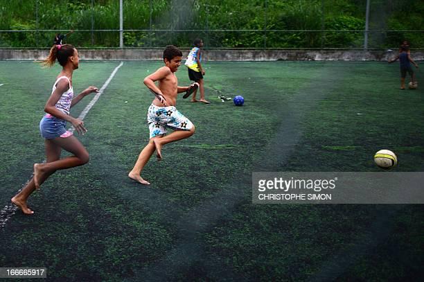 Children play football on a field in the Cidade de Deus shantytown Rio de Janeiro Brazil on April 13 2013 AFP PHOTO/CHRISTOPHE SIMON