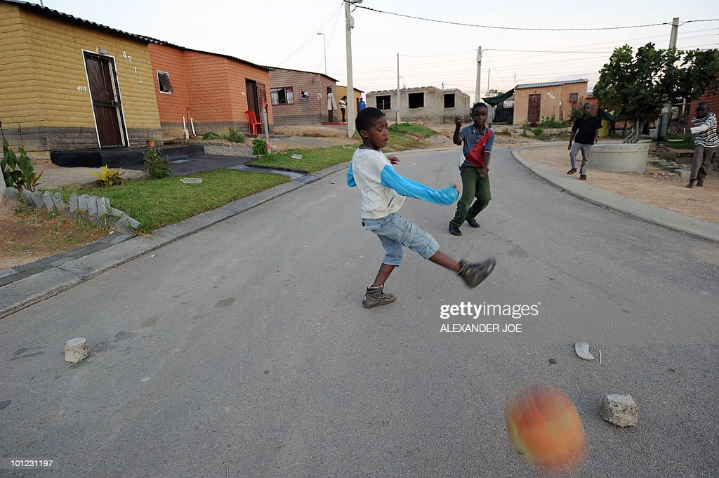 Children play football on the Corner of League and Match street, in Alexandra, north of Johannesburg on May 8, 2010. All of the street in the township have football flavour names like Striker street or Football street.