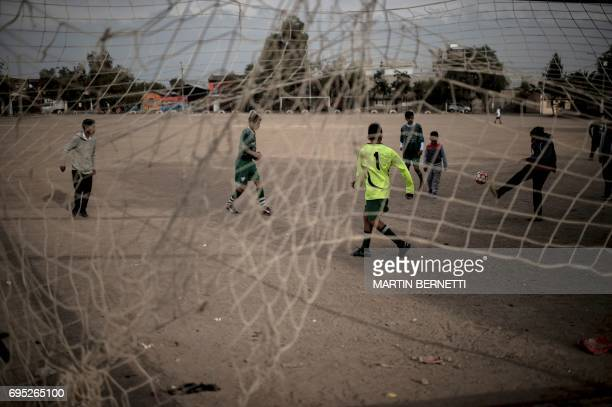 TOPSHOT Children play football on the dirt field of the Rodelino Roman club in Santiago on May 7 2017 in the neighbourhood where Chilean football...