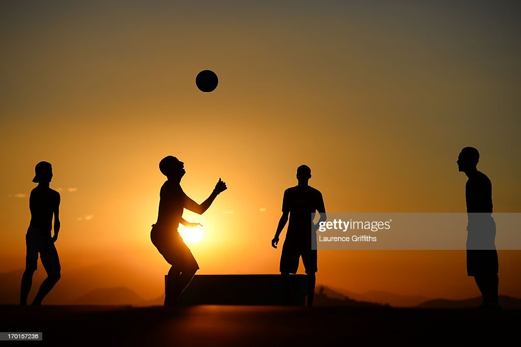 Children play football on the rooftops of a Favela at sunset on June 7, 2013 in Rio de Janeiro, Brazil.
