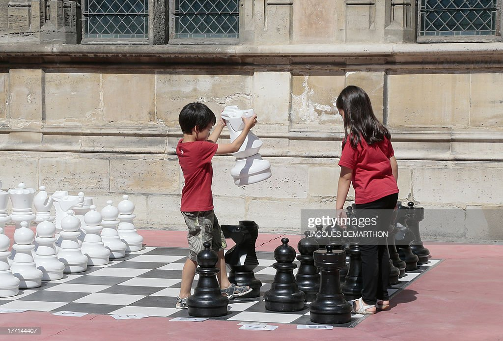 Children play giant chess in the Cluny museum's courtyard in Paris, on August 21, 2013.