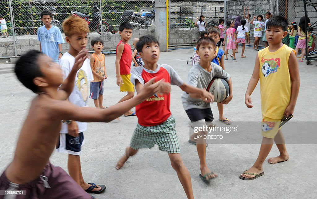 Children play in a basketball court in Manila on January 3, 2013. A Catholic couple has asked the Philippines' top court to stop a historic birth control law, their lawyer said on January 3, in the first of many legal challenges church leaders have vowed against the measure.