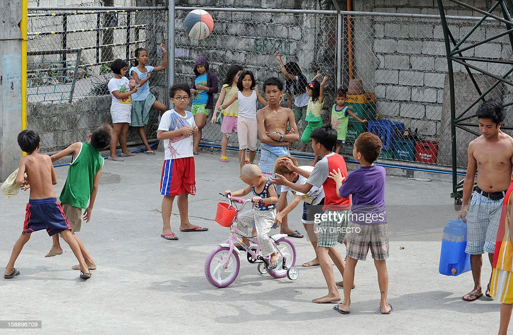 Children play in a basketball court in Manila on January 3, 2013. A Catholic couple has asked the Philippines' top court to stop a historic birth control law, their lawyer said on January 3, in the first of many legal challenges church leaders have vowed against the measure. AFP PHOTO / JAY DIRECTO